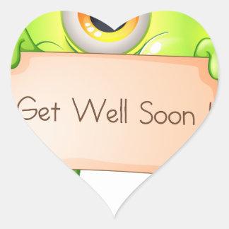A green monster holding a get-well-soon signage heart sticker
