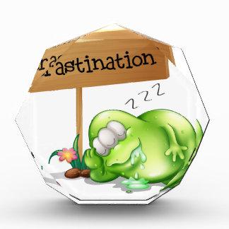 A green monster procrastinating beside a signboard acrylic award