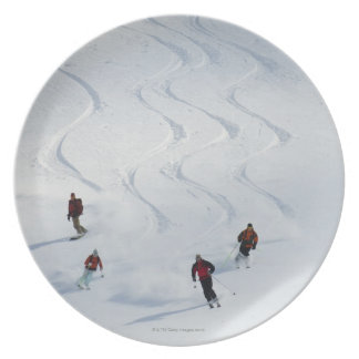 A group of backcountry skiers follow their guide dinner plate