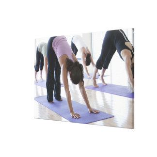 a group of women practicing yoga in a bright canvas print
