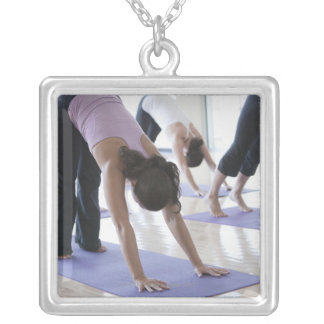 a group of women practicing yoga in a bright silver plated necklace