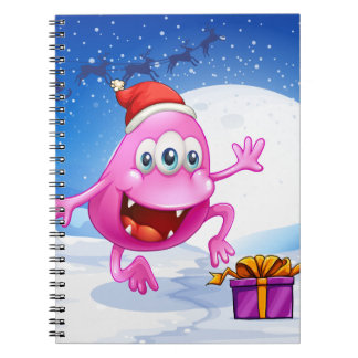 A happy pink beanie monster wearing Santa's hat Notebook