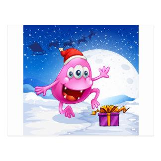 A happy pink beanie monster wearing Santa's hat Postcard