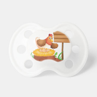 A hen laying eggs BooginHead pacifier