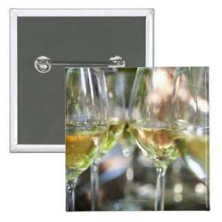 A host pours glasses of torrontes for guests at pinback button