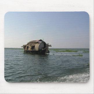 A houseboat moving placidly through a coastal lake mouse pad
