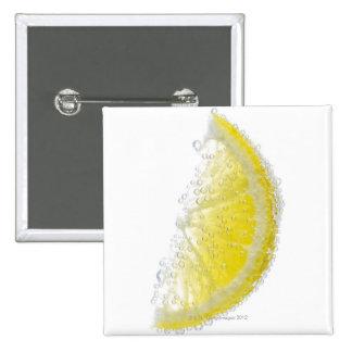 A juicy ripe organic lemon wedge fruit submerged pins