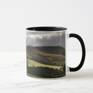 A Landscape With Rolling Hills And Clouds Overhead Mug