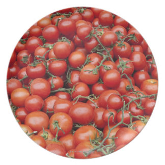 A large crop of tomato on a market stall in party plates