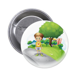 A little boy at the road across the high buildings 2 inch round button