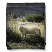 a little white lamb behind a fence in a field drawstring bag