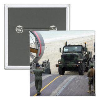 A loadmaster guides a Marine 7-ton truck Button