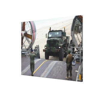 A loadmaster guides a Marine 7-ton truck Canvas Print