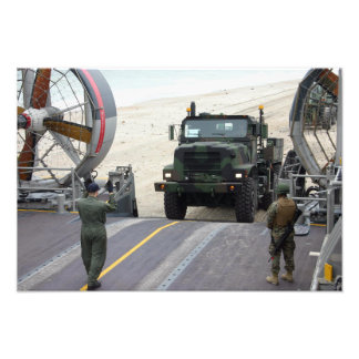 A loadmaster guides a Marine 7-ton truck Photographic Print
