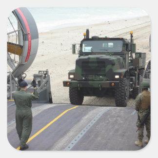 A loadmaster guides a Marine 7-ton truck Square Sticker