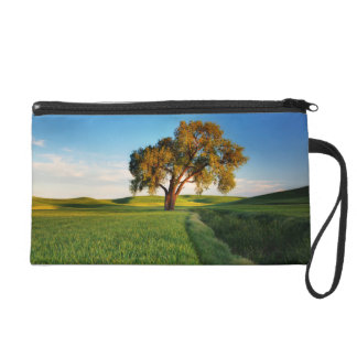A lone tree surrounded by rolling hills of wheat wristlet purse