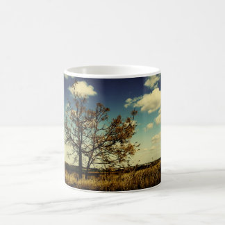 A lonely tree in a yellow dry field coffee mug