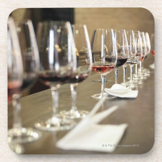 A long row of wine glasses set up so a large beverage coaster