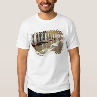 A long row of wine glasses set up so a large t shirt