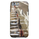 A long row of wine glasses set up so a large tough iPhone 6 case