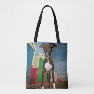 A Lurcher Standing In Front Of Some Beach Huts Tote Bag