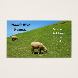 A lush green pasture with two sheep grazing business card