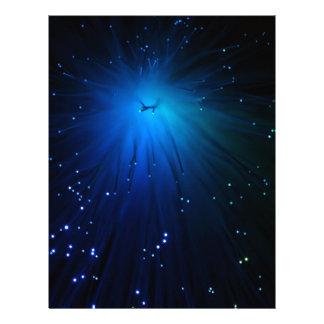 A macro photo of illuminated optical fibers. letterhead