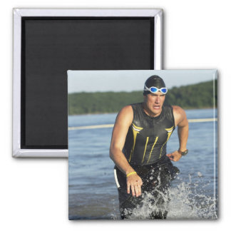 A male athelete running out of the water while 2 magnets