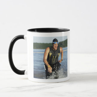 A male athelete running out of the water while 2 mug