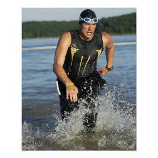 A male athelete running out of the water while 2 poster
