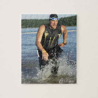 A male athelete running out of the water while 2 puzzles