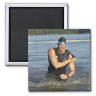 A male athelete running out of the water while refrigerator magnets