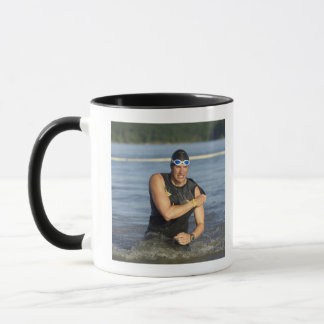 A male athelete running out of the water while mug