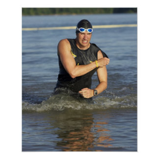 A male athelete running out of the water while poster