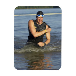 A male athelete running out of the water while magnets