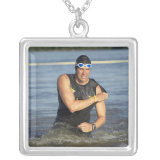 A male athelete running out of the water while silver plated necklace