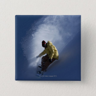 A male snowboarder catches last light on a button