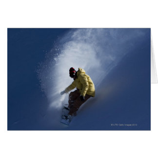 A male snowboarder catches last light on a card