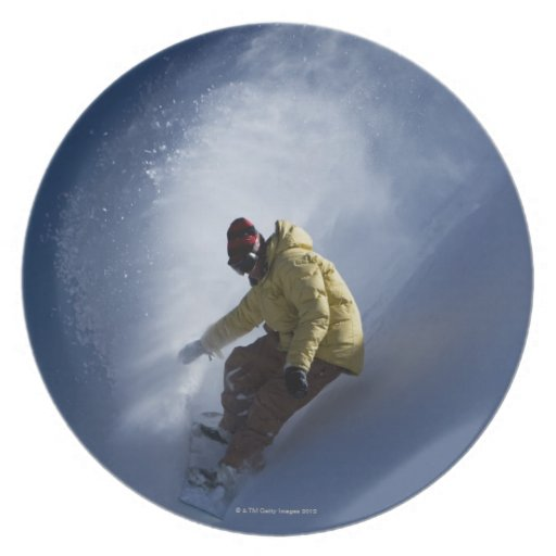 A male snowboarder catches last light on a dinner plates