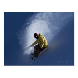 A male snowboarder catches last light on a postcard