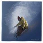A male snowboarder catches last light on a tile