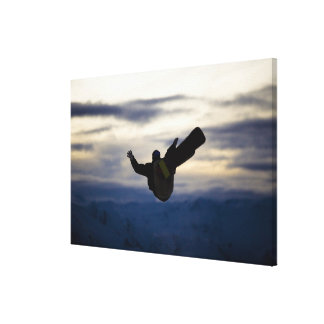 A male snowboarder does a back flip while riding canvas print