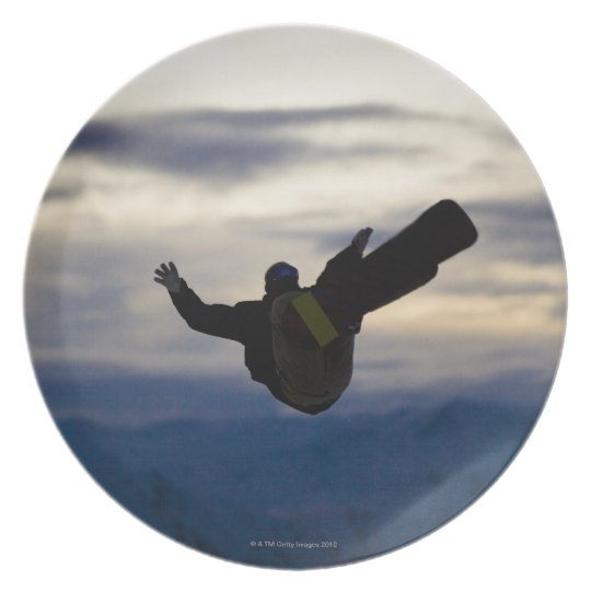 A male snowboarder does a back flip while riding dinner plate