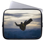 A male snowboarder does a back flip while riding laptop sleeve