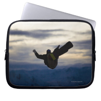 A male snowboarder does a back flip while riding laptop sleeves