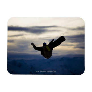 A male snowboarder does a back flip while riding magnet