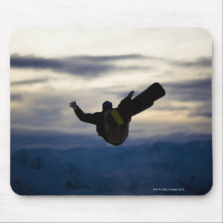 A male snowboarder does a back flip while riding mouse pad