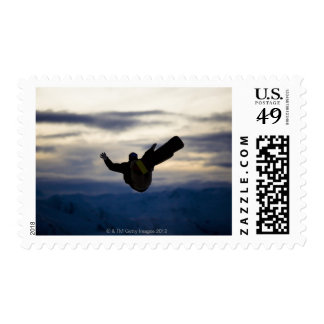 A male snowboarder does a back flip while riding postage