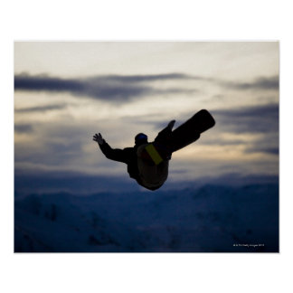 A male snowboarder does a back flip while riding poster
