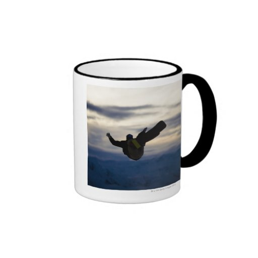 A male snowboarder does a back flip while riding ringer mug
